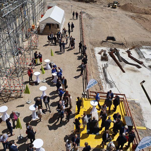 Etwa 100 Gäste feiern gemeinsam die Grundsteinlegung von Haus 1 in der Baugrube der Neuen Mitte Porz © Jasmin Schwarz