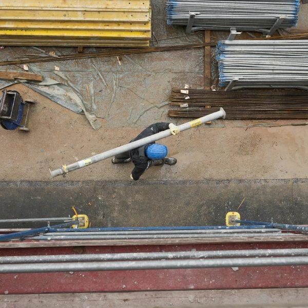 Ein Bauarbeiter trägt eine Rundrohrstütze © Dörthe Boxberg